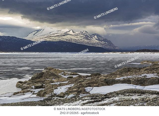 View over Stora sjöfallets national park in spring time, snow and ice on the water, mount Akka in background, cloudy weather, Stora sjöfallets national park