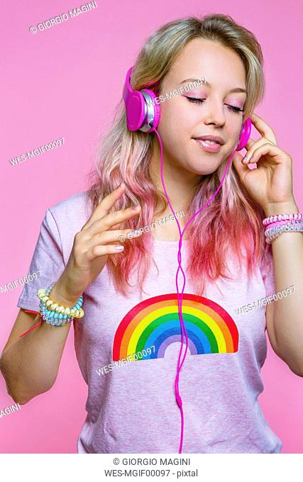 Portrait of young woman listening to music with headphones in front of pink background