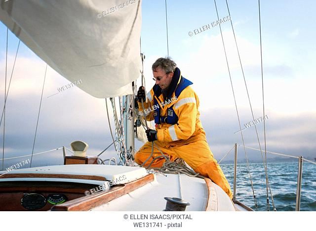 Sailor in yellow foul weather gear pulling on the halyard to raise the mainsail as he heads into cloudy weather in his sailboat