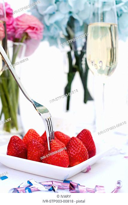Close-up of strawberry and fork placed on table with wine glass and flowers in background