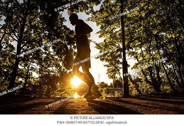 07.08.2018, Berlin: Against the rising sun, the jogger can only be seen as a silhouette on the banks of the Spree. Photo: Paul Zinken/dpa