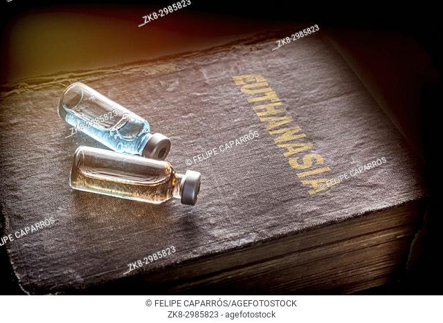 Two vials with medicine on an old book of euthanasia, conceptual image