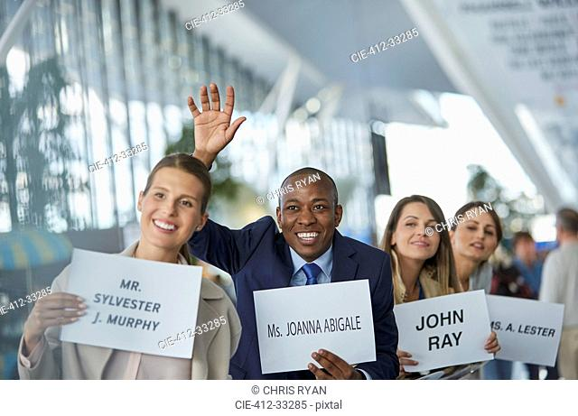 Chauffeurs with welcome signs smiling and waving in a row at airport