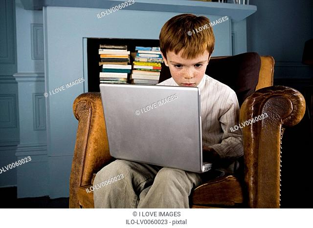 boy sitting in armchair using laptop computer
