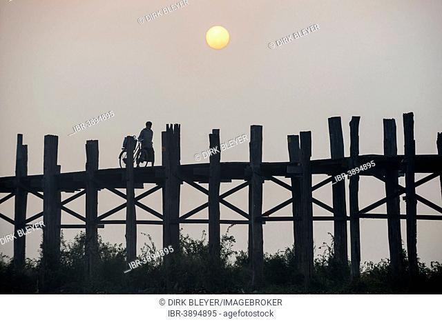 Man with a bicycle on a teak bridge, U Bein Bridge over Taungthaman Lake at sunrise, Amarapura, Mandalay Division, Myanmar