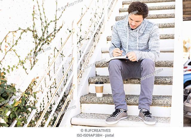 Young man sitting on steps writing