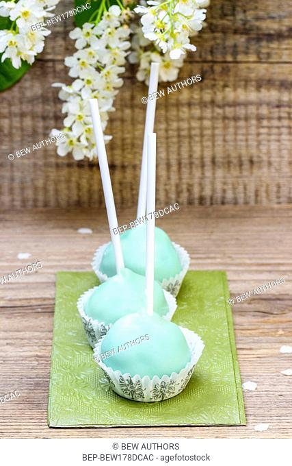 Pastel green cake pops in spring setting. Cherry blossom on wooden background, party table