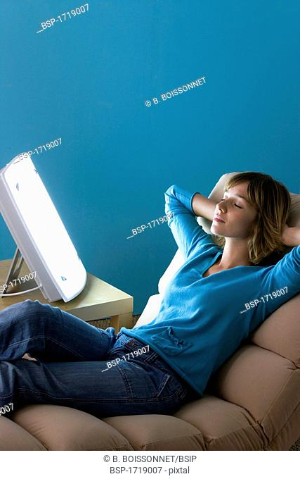 WOMAN LIGHT THERAPY Model. Light therapy lamps emit white light imitating daylight. They are used, between among other things