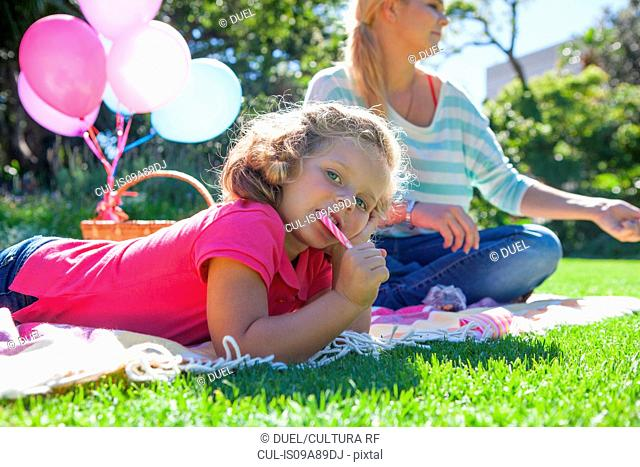 Girl eating candy cane on blanket in garden