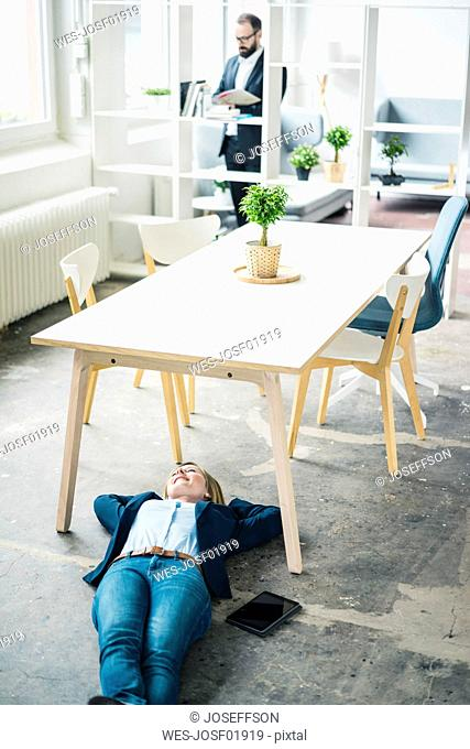 Smiling businesswoman lying on the floor in office