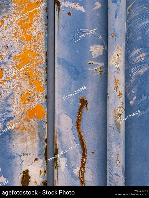 Detail of peeling paint and markings on colorfully painted industrial cargo container