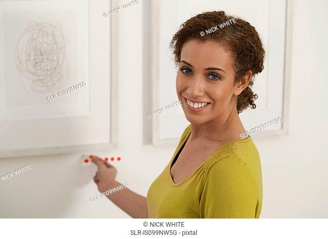 Art dealer placing sold dots under artwork in gallery