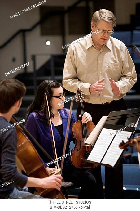 Professor instructing college string quartet