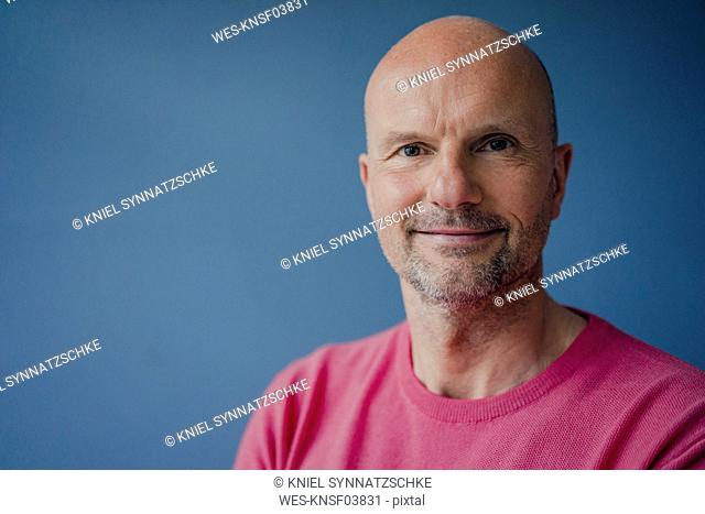 Portrait of smiling mature man wearing pink pullover