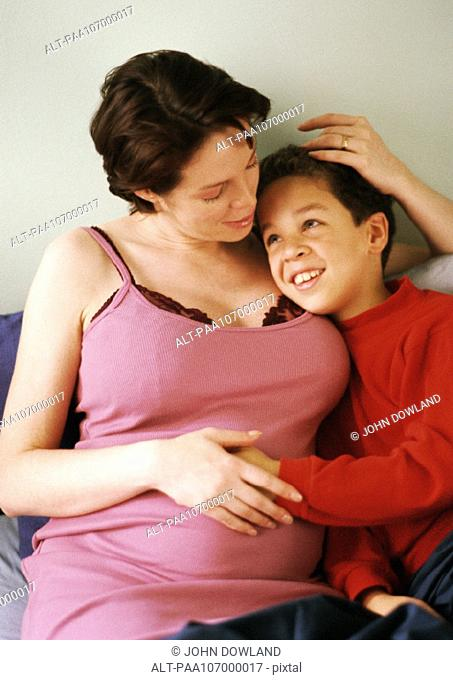 Pregnant woman sitting with arm around child