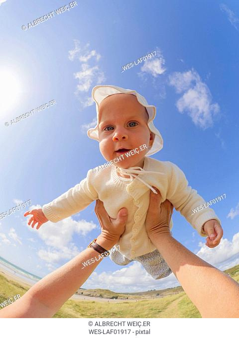 Portrait of baby girl holding aloft by her mother