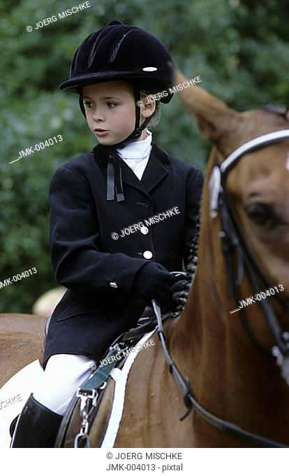 A little girl, 5-10 years old, riding a horse at a horse show