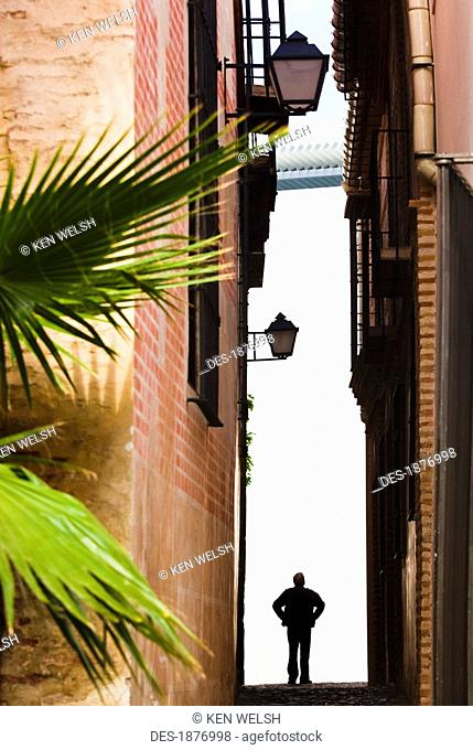 malaga, andalusia, spain, silhouetted figure of a man in a narrow street in costa del sol