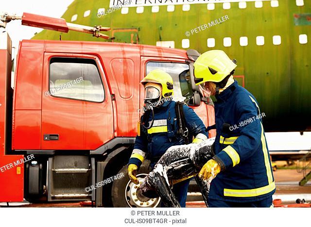 Firemen training, firemen in breathing apparatus carrying equipment