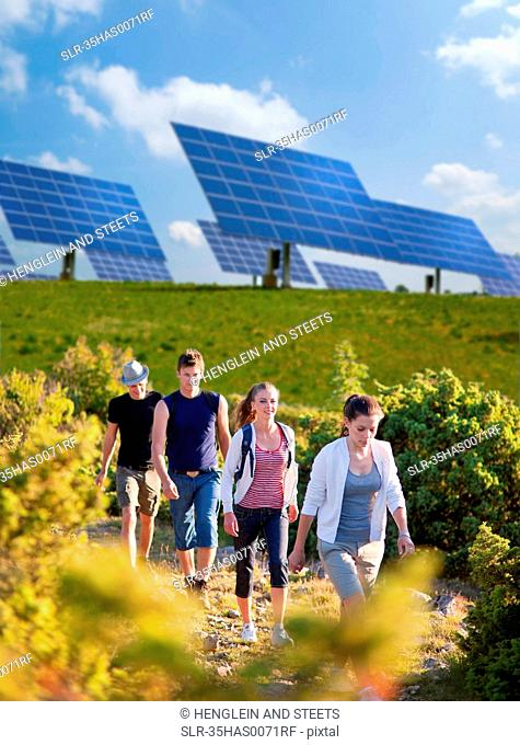 People walking by solar panels
