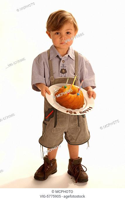 Ein kleiner Junge in Lederhose mit einem selbstgebackenen Kuchen fuer die Mutti, 2006 - Germany, 01/03/2006