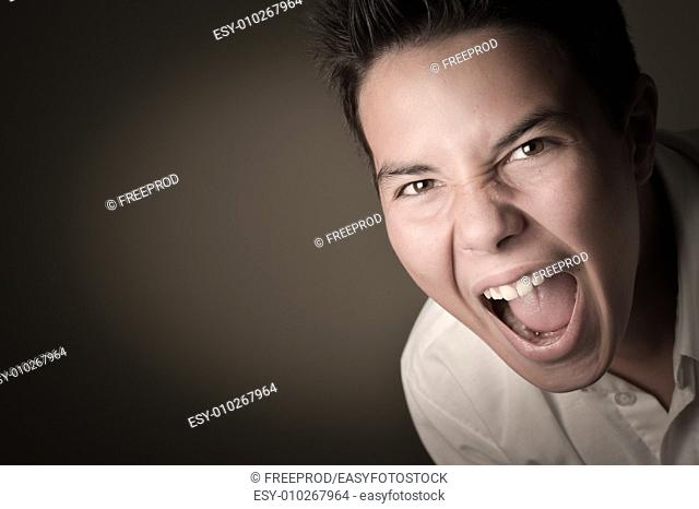 Laughing boy cring, shouting, screaming, hysteria on a brown background
