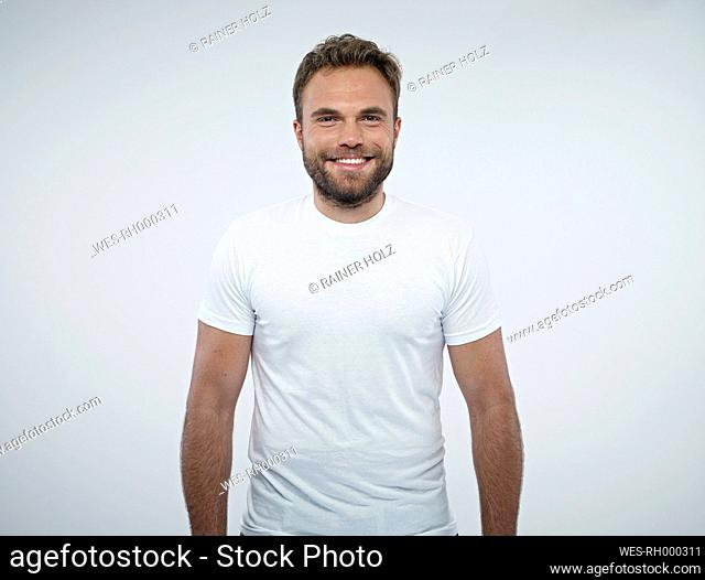 Portrait of smiling man in front of white background