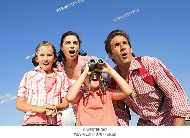 Italy, South Tyrol, Family with children 6-7 10-11, girl looking through binoculars, portrait