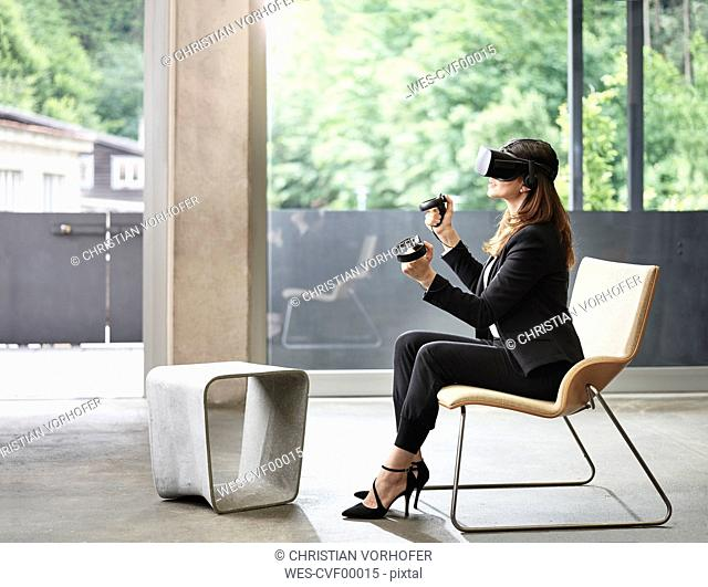 Businesswoman wearing VR glasses sitting on chair