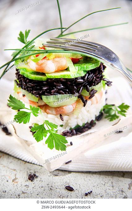 Presentation of a second tower gourmet dish of white rice and black with shrimp and zucchini