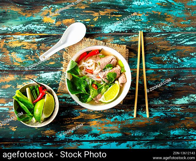 Traditional Vietnamese soup Pho bo with herbs, meat, rice noodles, broth. Pho bo in bowl with chopsticks, spoon. Top view