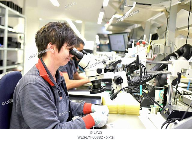 Woman using a microscope for the quality control in the manufacturing of circuit boards for the electronics industry