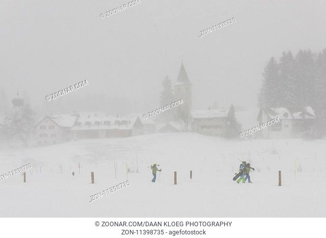 Parpan, Switzerland - January 4, 2017: Skiers in snow storm in the small town of Parpan with church in kanton Graubunden in Switzerland