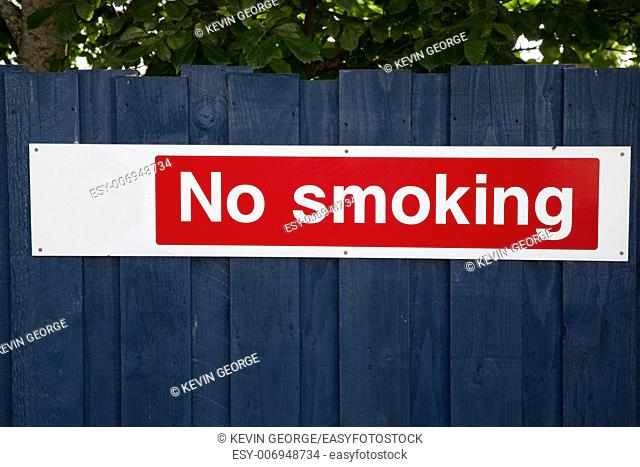 Red No Smoking Sign on Blue Fence