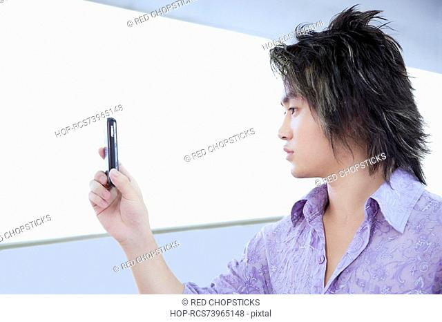 Close-up of a young man taking a picture with a mobile phone