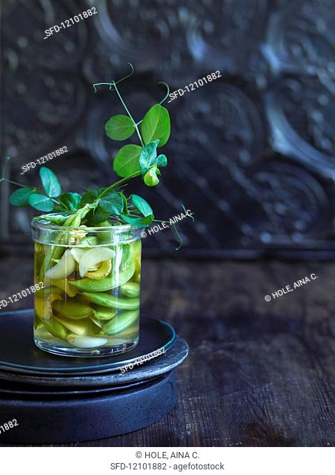 Pickled sugar snap peas with ginger and garlic in a glass