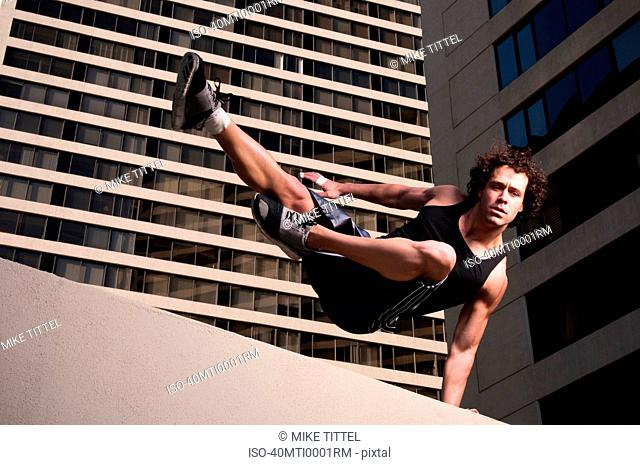 Athlete jumping over urban wall
