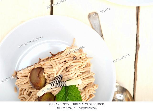 fresh baked chestnut cream cake dessert over rustic white wood table