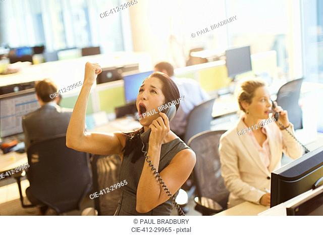 Exuberant woman on telephone celebrating good news in office