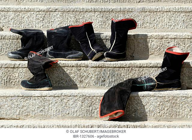 Black Tibetan monk boots on the stairs in front of the Assembly Hall, Tibetan Dukhang, the Labarang Monastery, Xiahe, Gansu, China, Asia