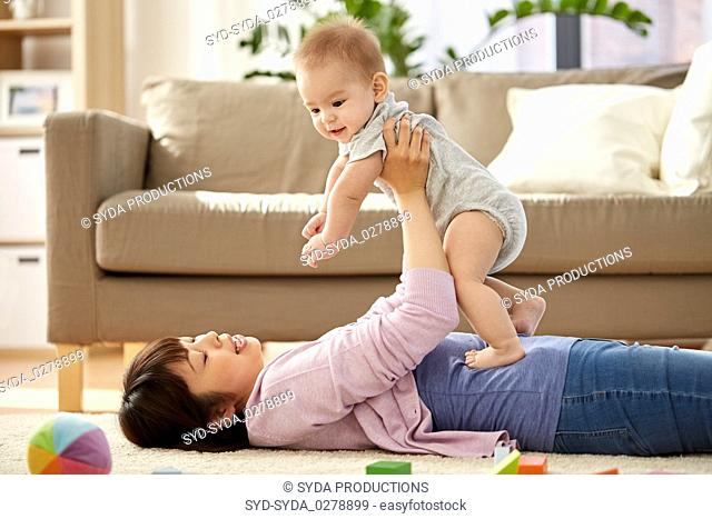 happy mother playing with little baby son at home
