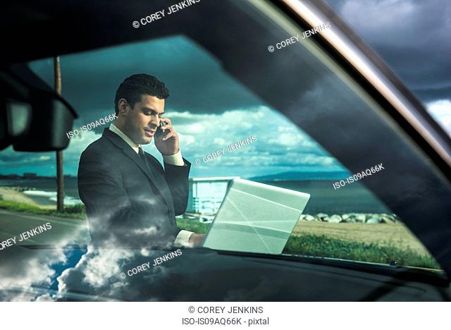 Businessman using laptop whilst talking on smartphone at coastal parking lot