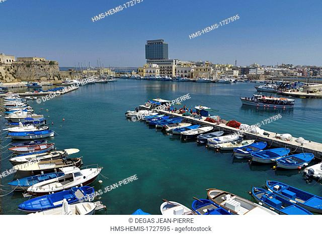 Italy, Puglia, Lecce province, Gallipoli, fishing port, blue boats alongside the quay with a boat for the background excursions