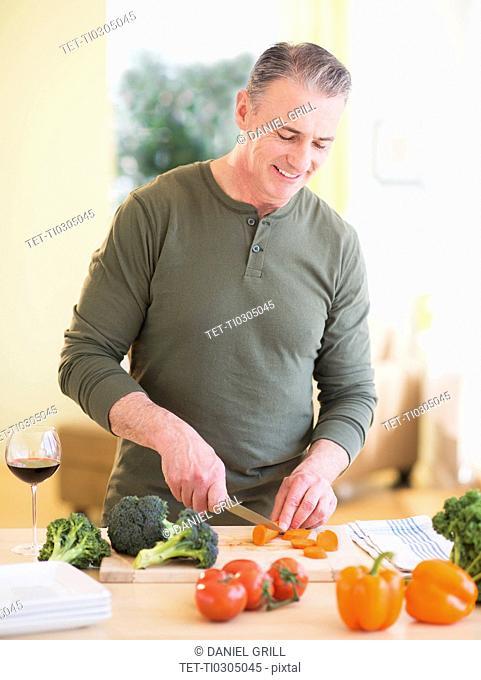 Portrait of man cutting vegetables