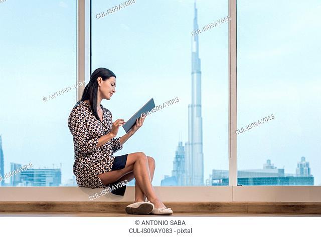 Businesswoman using digital tablet sitting at window, Dubai, United Arab Emirates