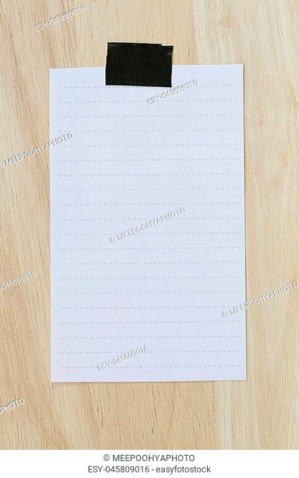 White paper blank or note paper on the brown wooden floor and You can input the message text in copy space