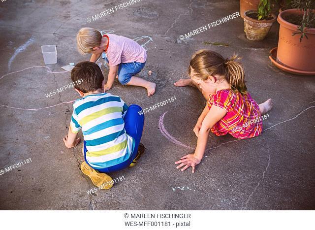 Germany, Northrhine Westphalia, Bornheim, Children playing and drawing in courtyard