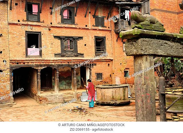 Woman sweeping on a square with Newari traditional architecture, Bhaktapur, Nepal