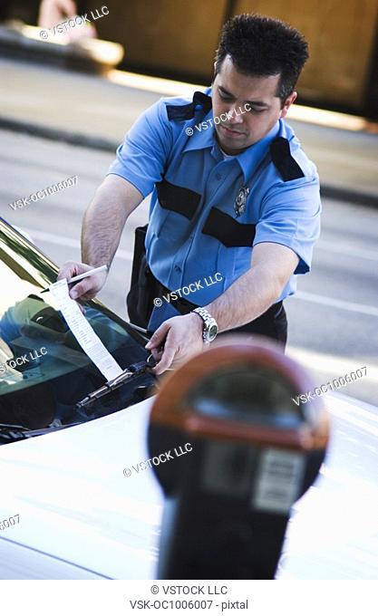 Policeman writing parking ticket