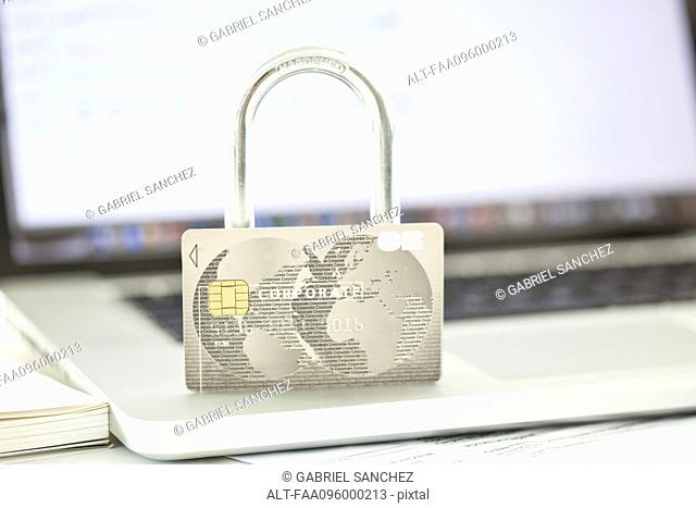 Credit card and lock resting on top of laptop computer representing internet security